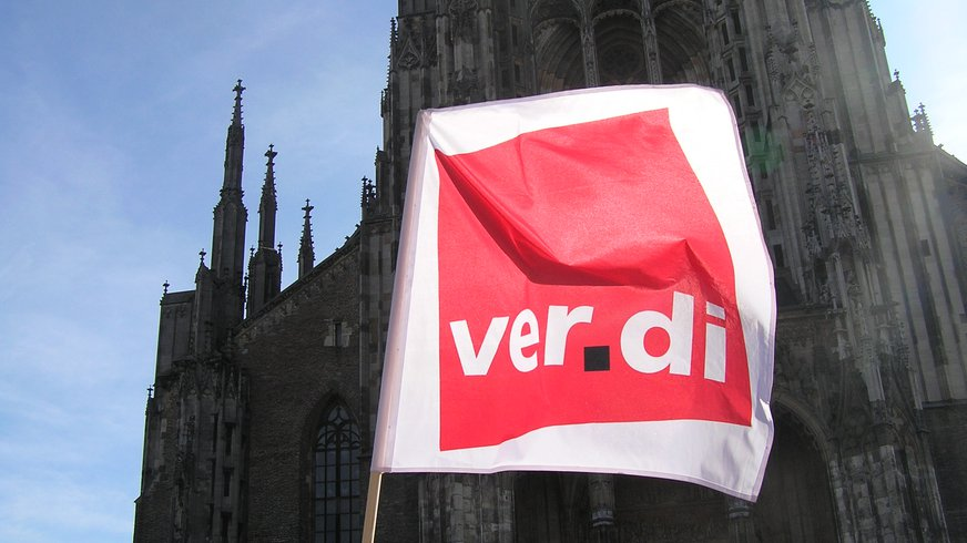 Ulmer Münster im Vordergrund die Fahne der Gewerkschaft verdi